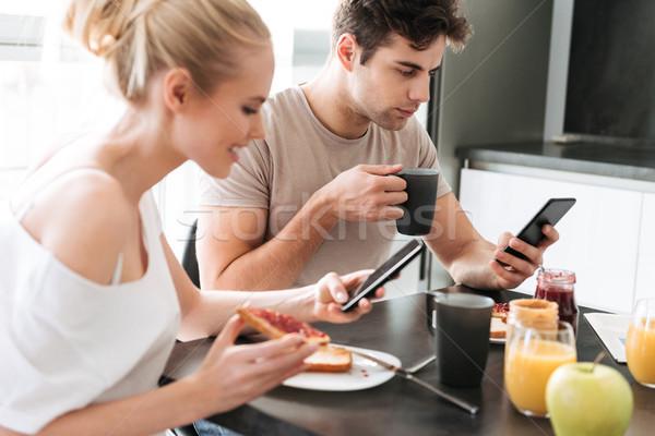 Csinos koncentrált szerelmespár reggeli konyha eszik Stock fotó © deandrobot