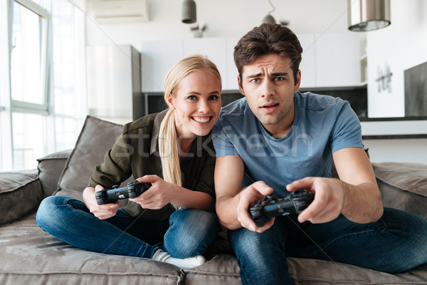 Young concentrated man and woman playing video games in living room Stock photo © deandrobot