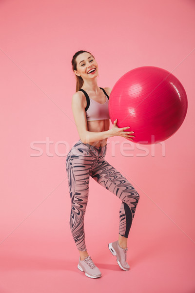 Full length image of Happy sportswoman posing with fitness ball Stock photo © deandrobot