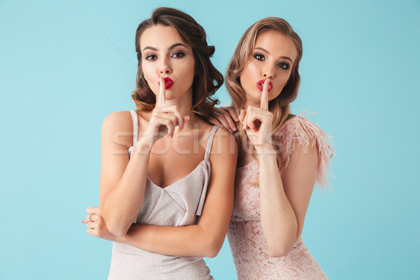 Shh! Image of two gorgeous women 20s wearing dresses and party m Stock photo © deandrobot