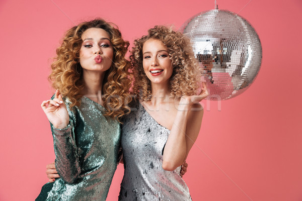 Two beautiful flirty women in shiny dresses Stock photo © deandrobot