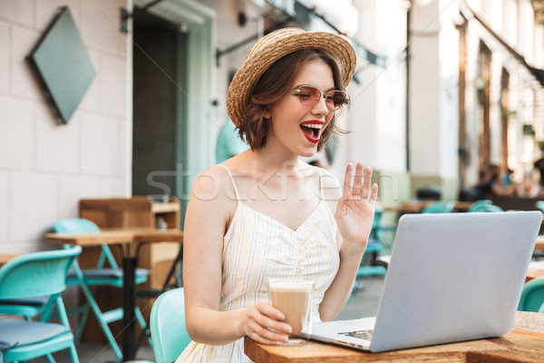 Woman in dress and straw hat talking by video call Stock photo © deandrobot