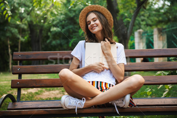 Delighted young girl reading a book Stock photo © deandrobot