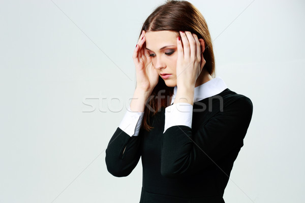Portrait of a young woman touching her head with headache Stock photo © deandrobot