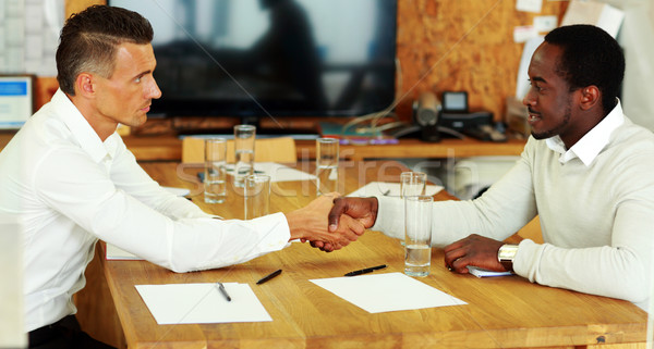 Young business man shaking hands with colleague across the table Stock photo © deandrobot
