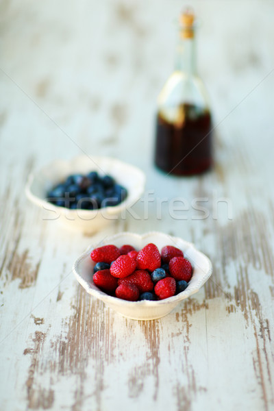 Mix of blueberries and strawberries in vintage plates with wine on the backgroud Stock photo © deandrobot