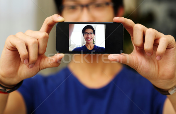 Happy asian man taking self picture with smartphone camera. Focus on smartphone Stock photo © deandrobot
