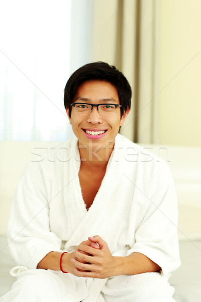 Smiling man in bathrobe sitting on the bed in bedroom Stock photo © deandrobot