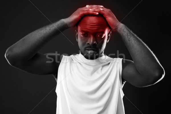 Frustrated african man touching his head over black background Stock photo © deandrobot