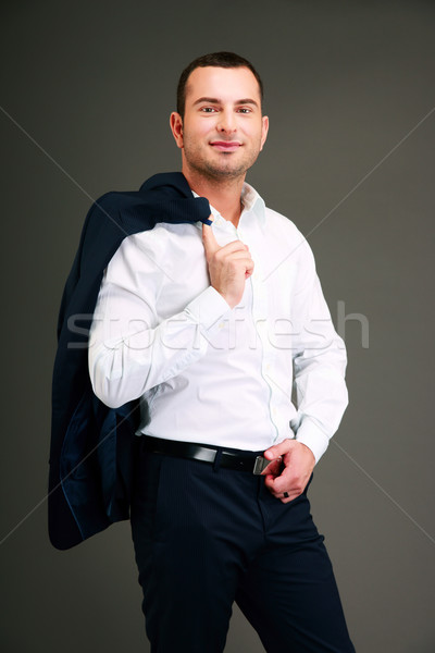 Portrait of a businessman holding his jacket over shoulder Stock photo © deandrobot