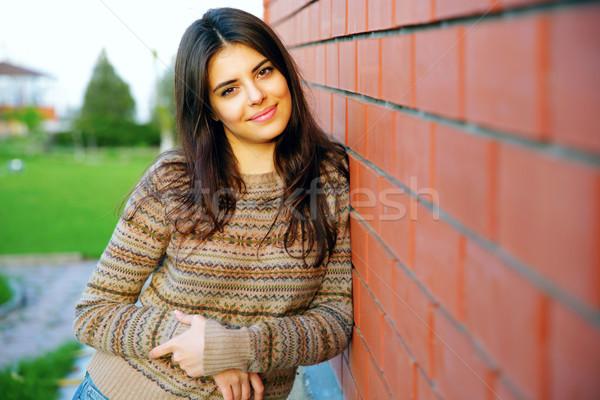 Gyönyörű boldog nő áll téglafal lány Stock fotó © deandrobot