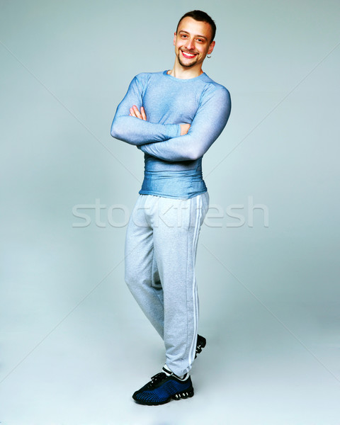 Full-length portrait of a happy man standing with arms folded on gray background Stock photo © deandrobot