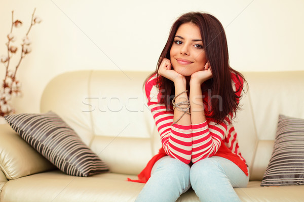 Smiling teen girl in colorful cloths sitting on the sofa and relaxing Stock photo © deandrobot
