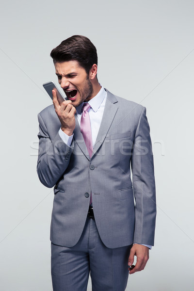 Confident businessman shouting on the phone Stock photo © deandrobot