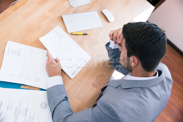 Businessman sitting at the table with documents Stock photo © deandrobot