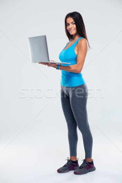 Portrait of a fitness woman using laptop Stock photo © deandrobot