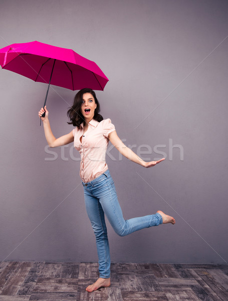 Surprised woman posing with umbrella Stock photo © deandrobot