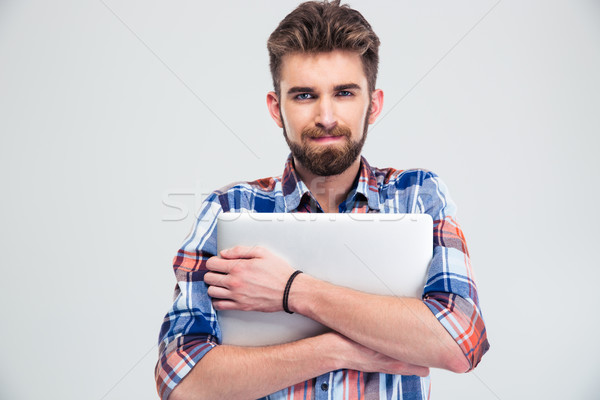 Unshaved handsome man holding laptop Stock photo © deandrobot