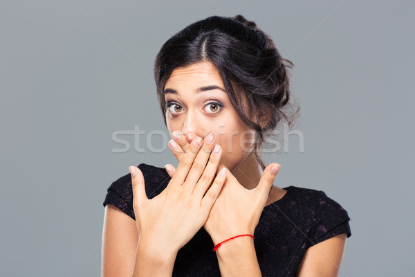 Portrait of a young woman covering her mouth Stock photo © deandrobot