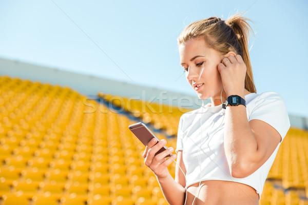 Stock photo: Woman using smartphone on stadium