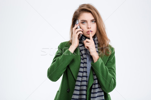 Woman talking on the phone and showing finger over lips Stock photo © deandrobot