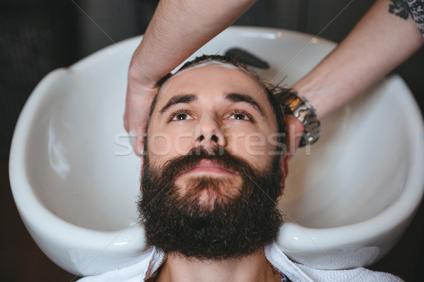 Hairstylist washing head of man with beard in barbershop Stock photo © deandrobot