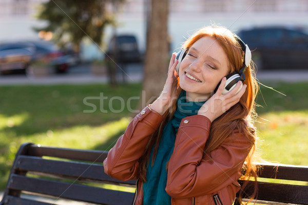 Content cheerful woman listening to music with eyes closed Stock photo © deandrobot