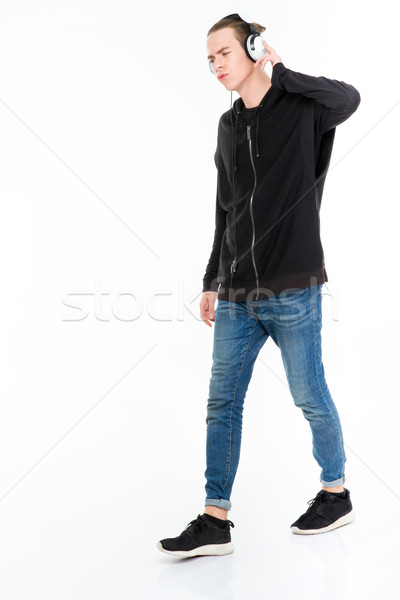 Young man listening music in headphones Stock photo © deandrobot