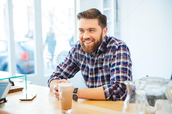 Homme séance table cappuccino souriant café Photo stock © deandrobot