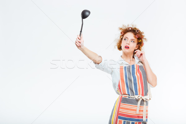 Housewife with curly hair in apron looking on soup ladle Stock photo © deandrobot