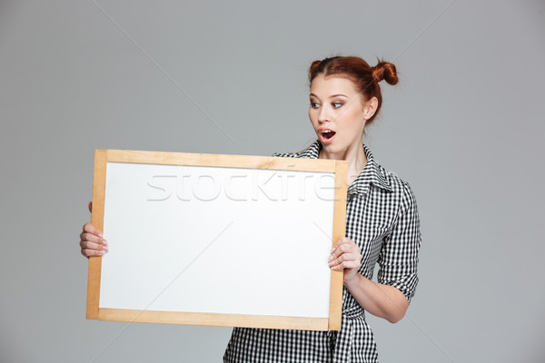 Amamzed cute woman holding and looking at blank whiteboard  Stock photo © deandrobot