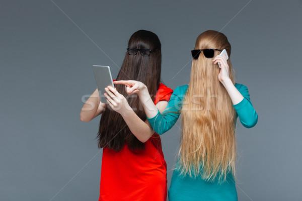 Duas mulheres coberto faces telefone móvel comprimido dois Foto stock © deandrobot