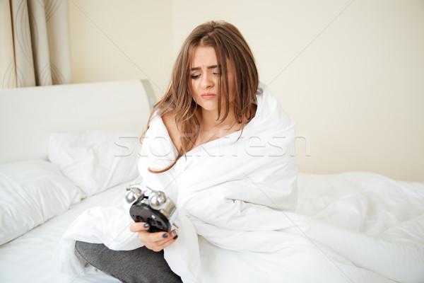 Sad woman holding alarm clock on the bed Stock photo © deandrobot