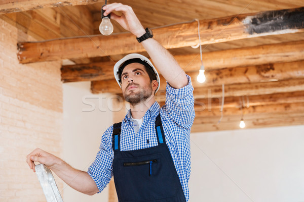 Builder fixing socket using ladder indoors Stock photo © deandrobot