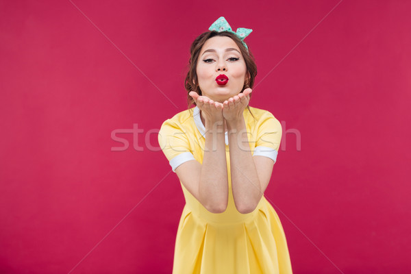 Happy pretty pinup girl in yellow dress sending a kiss Stock photo © deandrobot