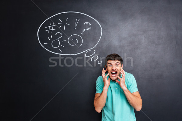 Crazy furious man yelling over blackboard background with speech bubble Stock photo © deandrobot