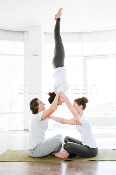 Deux jeunes femmes homme acrobatique yoga poste Photo stock © deandrobot