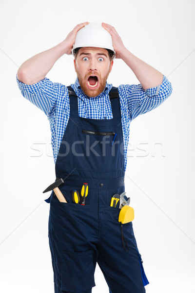 Astonished shocked young builder in helmet staning with mouth opened Stock photo © deandrobot