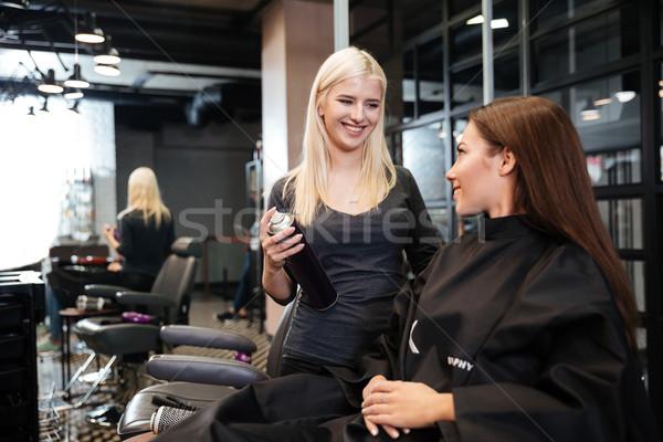 Hairdresser with hair spray fixating client hairdo at salon Stock photo © deandrobot