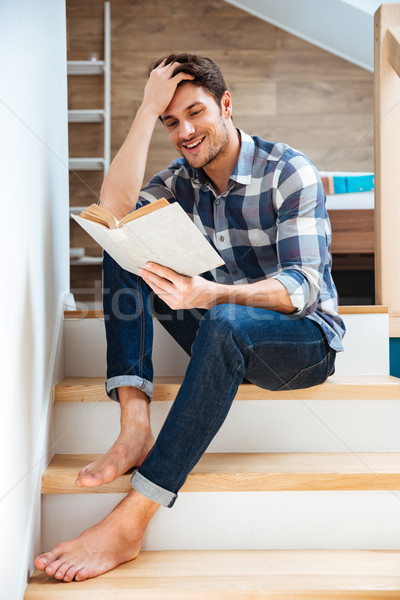 Young handsome man reading book while sitting on the stairs Stock photo © deandrobot