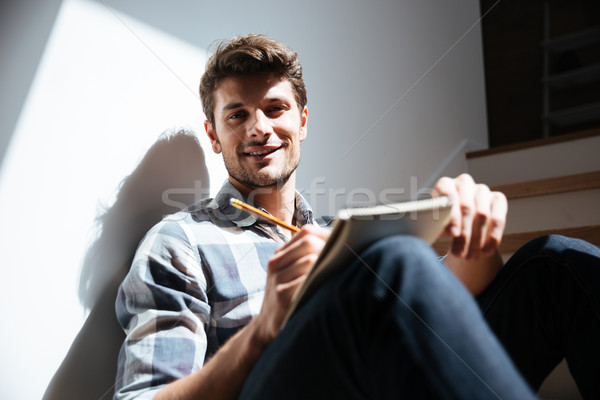 Happy young man sitting the floor and writing in notepad Stock photo © deandrobot