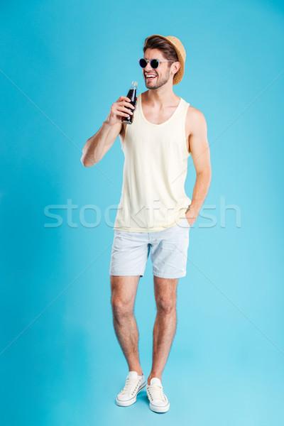 Alegre moço em pé potável soda Foto stock © deandrobot