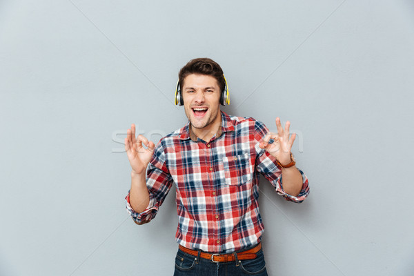 Man in headphones showing ok sign and listening to music Stock photo © deandrobot