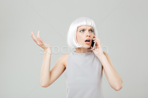 Puzzled worried woman in blonde wig talking on mobile phone Stock photo © deandrobot