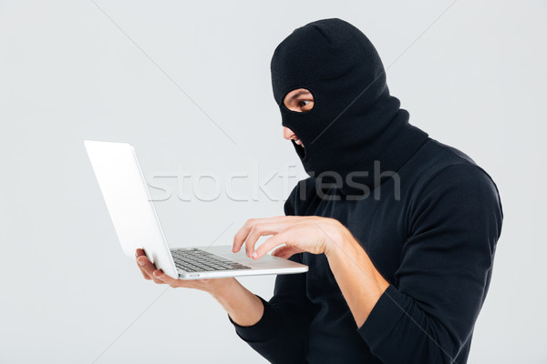 Portrait of man in balaclava standing and using laptop Stock photo © deandrobot