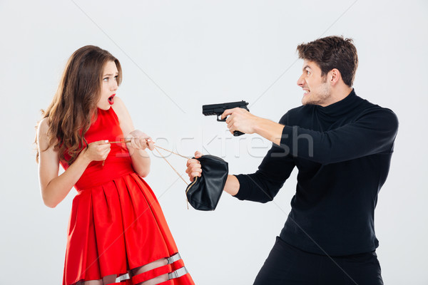 Man theif stealing young woman bag and threatening with gun Stock photo © deandrobot