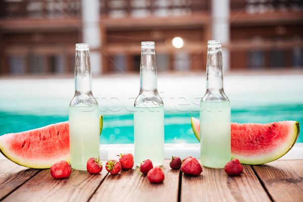 Concept photo alcohol bottles with fresh strawberries halves of watermelon Stock photo © deandrobot