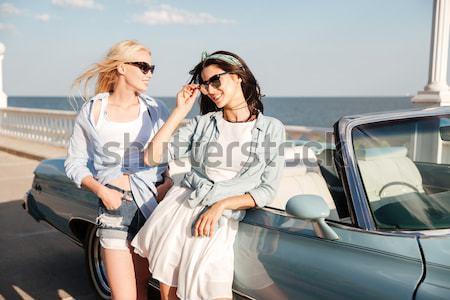 Dos feliz las mujeres jóvenes pie espera cabriolé Foto stock © deandrobot