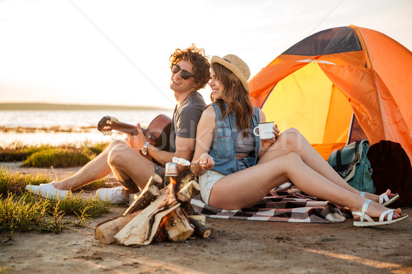 Couple sitting near campfire and playing guitar Stock photo © deandrobot