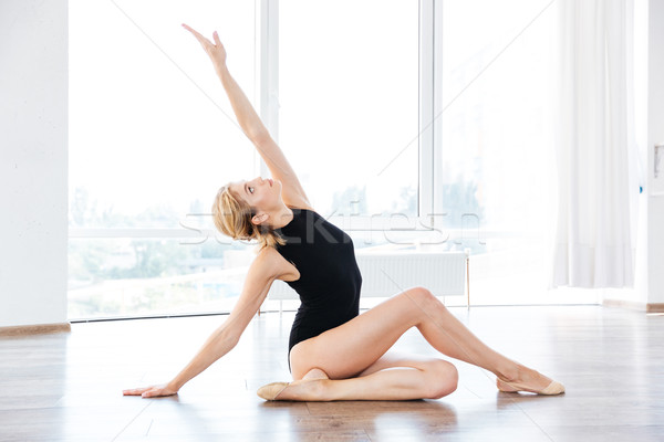 Woman ballerina sitting and stretching in dance class Stock photo © deandrobot